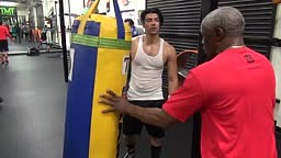 Floyd Mayweather instructing Aldo Uribe on the heavy bag inside Mayweather Boxing Club