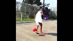 Black girl in princess dress and crown playing basketball